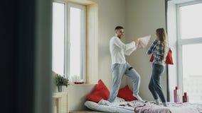 Los pares felices y cariñosos jovenes luchan las almohadas en cama en casa por la mañana imágenes de archivo libres de regalías
