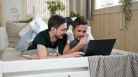 Los pares gay jovenes felices de hombres están utilizando el ordenador portátil moderno que miente en cama en el dormitorio Pares almacen de metraje de vídeo