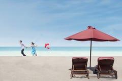 Los pares hermosos corren cerca de sillas y del paraguas de playa fotos de archivo