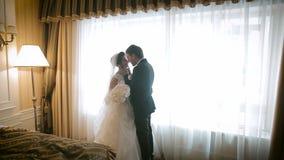 Los pares hermosos de la boda acercan a la ventana almacen de metraje de vídeo