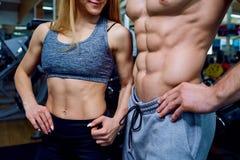 Los pares hermosos del cuerpo de deportes hinchan el primer en gimnasio Foto de archivo libre de regalías