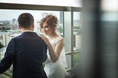 Los pares hermosos del recién casado acercan a la ventana con paisaje de la ciudad Imagen de archivo libre de regalías
