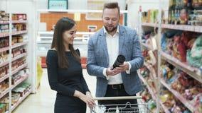 Los pares hermosos eligen productos en supermercado almacen de video