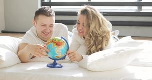 Los pares hermosos en amor en cama están mirando el globo que la hace girar y que señala al azar eligiendo un lugar para viajar metrajes