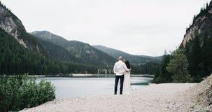Los pares hermosos en el amor, permaneciendo el primer con uno a, lago asombroso del fondo y perfeccionan las montañas verdes metrajes