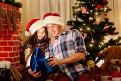 Los pares hermosos en los sombreros de Papá Noel abren un regalo en el cuarto con foto de archivo libre de regalías
