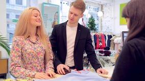 Los pares hermosos jovenes eligen la ropa en la tienda y van al cashdesk almacen de metraje de vídeo