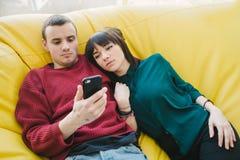 Los pares hermosos jovenes en el amor que miente en una silla amarilla y utilizan un teléfono móvil en su tiempo libre Foto de archivo libre de regalías