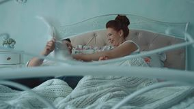 Los pares hermosos jovenes que se divierten en cama, luchan por los amortiguadores, riendo, c?mara lenta metrajes