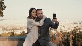 Los pares hermosos jovenes toman la foto del selfie contra el panorama de Roma, Italia El hombre feliz besa a la mujer y abraza imagenes de archivo