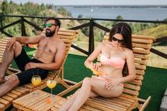Los pares hermosos se sientan en sunbeds y la refrigeración La muchacha puso una cierta protección poner crema en piel y la frota imagen de archivo libre de regalías