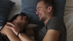 Los pares hermosos y cariñosos jovenes hablan y abrazan en cama mientras que despiertan por la mañana Opinión superior el hombre  almacen de metraje de vídeo