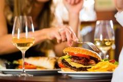 Los pares felices en restaurante comen los alimentos de preparación rápida Imágenes de archivo libres de regalías