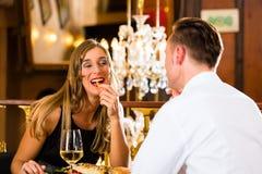 Los pares felices en restaurante comen los alimentos de preparación rápida Foto de archivo libre de regalías