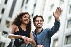 Los pares interraciales del negocio tienen una conversación en ciudad moderna imagen de archivo libre de regalías