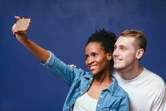 Los pares interraciales felices hacen el selfie con el móvil Fotografía de archivo libre de regalías