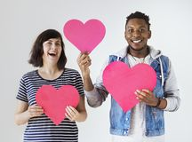 Los pares interraciales felices que llevan a cabo corazones rojos aman y concepto de la relación Foto de archivo libre de regalías