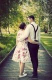 Los pares jovenes abrazan mientras que se colocan en la trayectoria de madera Foto de archivo