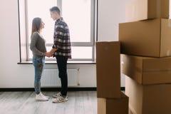 Los pares jovenes acertados abrazan después de mover al nuevo lugar agradable y de abarcamiento, alrededor son las cajas del cart Imagen de archivo libre de regalías