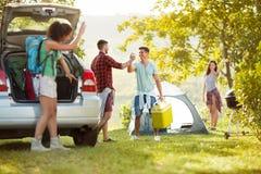 Los pares jovenes acogieron con satisfacción a sus amigos se unen a los en una acampada Foto de archivo