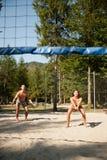 Los pares jovenes activos juegan voleo de la playa en día caliente del wimmer Fotografía de archivo