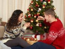 Los pares jovenes adornan el árbol de abeto de la Navidad Interior del hogar con los regalos Concepto del día de fiesta del Año N Foto de archivo libre de regalías