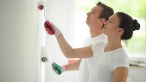 Los pares jovenes adornan su nuevo apartamento Están pintando la pared almacen de video