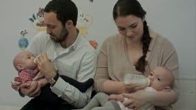 Los pares jovenes alimentan a gemelos recién nacidos de una botella