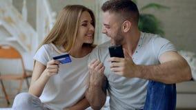 Los pares jovenes atractivos con compras de la tarjeta del smartphone y de crédito en Internet se sientan en cama en casa foto de archivo