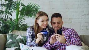 Los pares jovenes atractivos con compras de la tarjeta del smartphone y de crédito en Internet se sientan en el sofá en sala de e fotografía de archivo libre de regalías