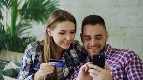 Los pares jovenes atractivos con compras de la tarjeta del smartphone y de crédito en Internet se sientan en el sofá en sala de e fotos de archivo