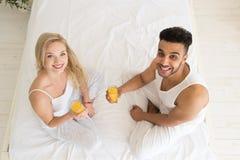 Los pares jovenes beben Juice Sitting In Bed anaranjado, el hombre hispánico de la sonrisa feliz y la opinión de ángulo superior  Imagenes de archivo
