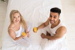 Los pares jovenes beben Juice Sitting In Bed anaranjado, el hombre hispánico de la sonrisa feliz y la opinión de ángulo superior  Foto de archivo