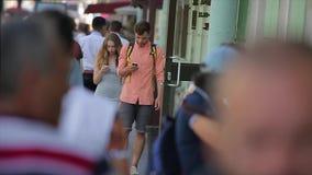 Los pares jovenes caminan a lo largo de la calle ocupada de la ciudad y miran sus smartphones en la cámara lenta almacen de video