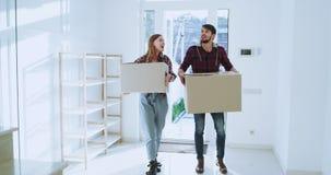 Los pares jovenes carismáticos que se mueven a una nueva casa moderna que sostienen las cajas grandes muy emocionadas ellos entra almacen de video