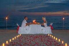 Los pares jovenes comparten una cena romántica con las velas Fotografía de archivo
