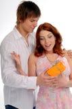 Los pares jovenes con el aerosol y el regalo Foto de archivo libre de regalías