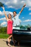 Los pares jovenes con el cabriolé en verano el día disparan Imagen de archivo