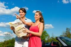 Los pares jovenes con el cabriolé en verano el día disparan Imagenes de archivo