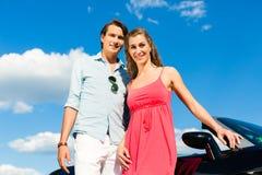 Los pares jovenes con el cabriolé en verano el día disparan Fotos de archivo