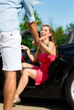 Los pares jovenes con el cabriolé en verano el día disparan Fotografía de archivo libre de regalías