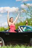 Los pares jovenes con el cabriolé en verano el día disparan Foto de archivo