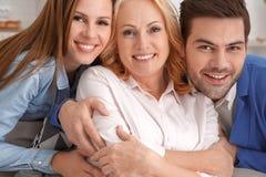 Los pares jovenes con la suegra en casa weekend el retrato de la familia imagenes de archivo