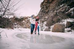 Los pares jovenes con las tazas de té caliente en sus manos celebran las manos, sonrisa y caminar a través de charco del agua der Imágenes de archivo libres de regalías