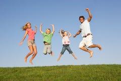Los pares jovenes con los niños saltan en un campo Fotos de archivo
