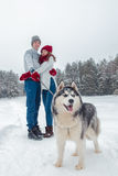 Los pares jovenes con un perro fornido que camina en invierno abarcamiento parquean, del hombre y de la mujer Foto de archivo libre de regalías