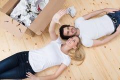 Los pares jovenes contentos se relajan en el piso Fotografía de archivo libre de regalías