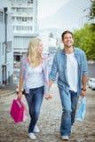 Los pares jovenes de la cadera en compras disparan caminar cuesta arriba Fotos de archivo