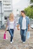 Los pares jovenes de la cadera en compras disparan caminar cuesta arriba Fotos de archivo libres de regalías