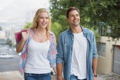 Los pares jovenes de la cadera en compras disparan caminar cuesta arriba Imagenes de archivo
